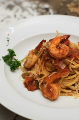 Ouzo marinated prawns cooked in a rich tomato and herb sauce on a bed of linguine.