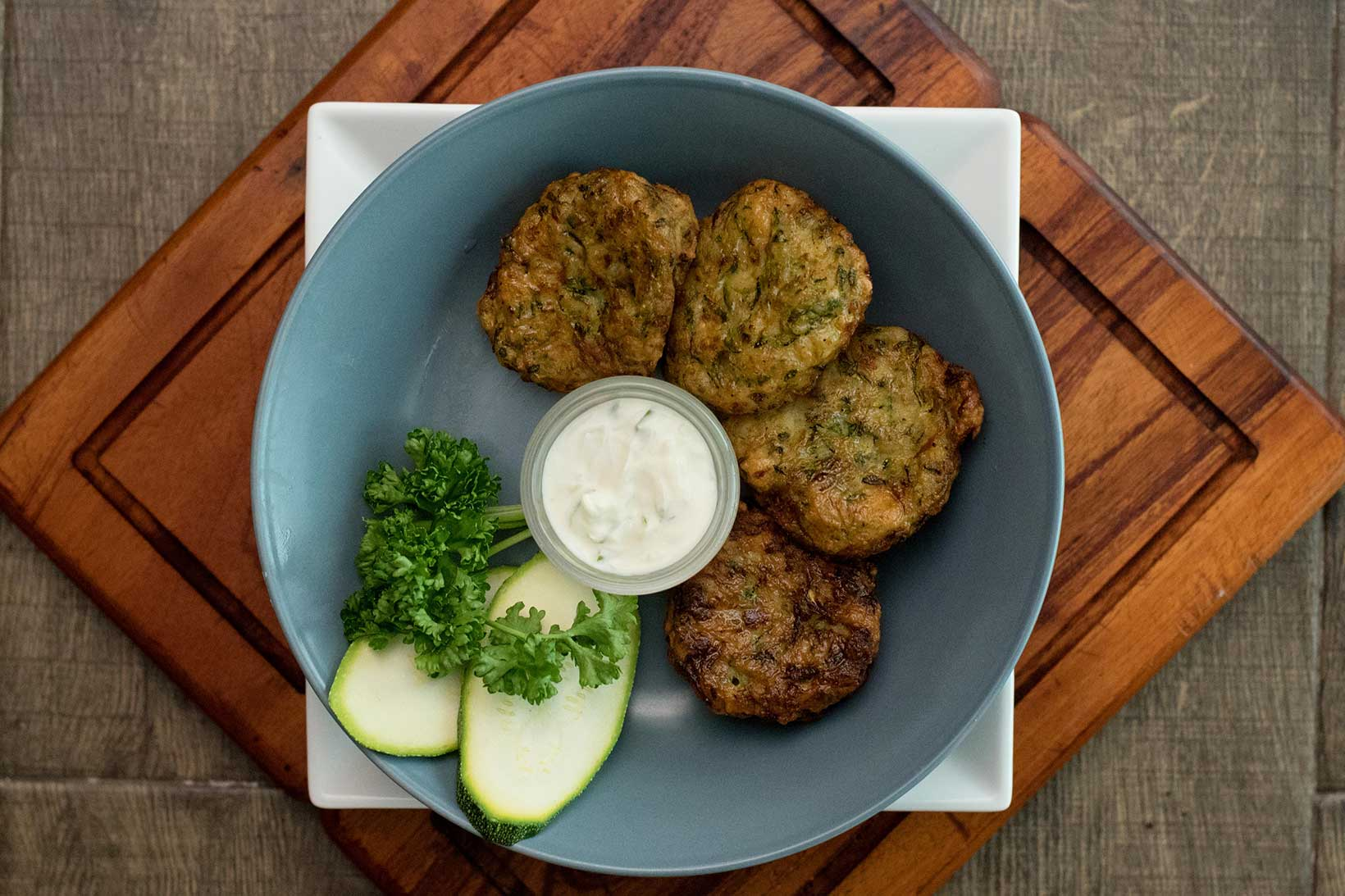 Pan fried zucchini fritters with tzatziki dipping sauce.