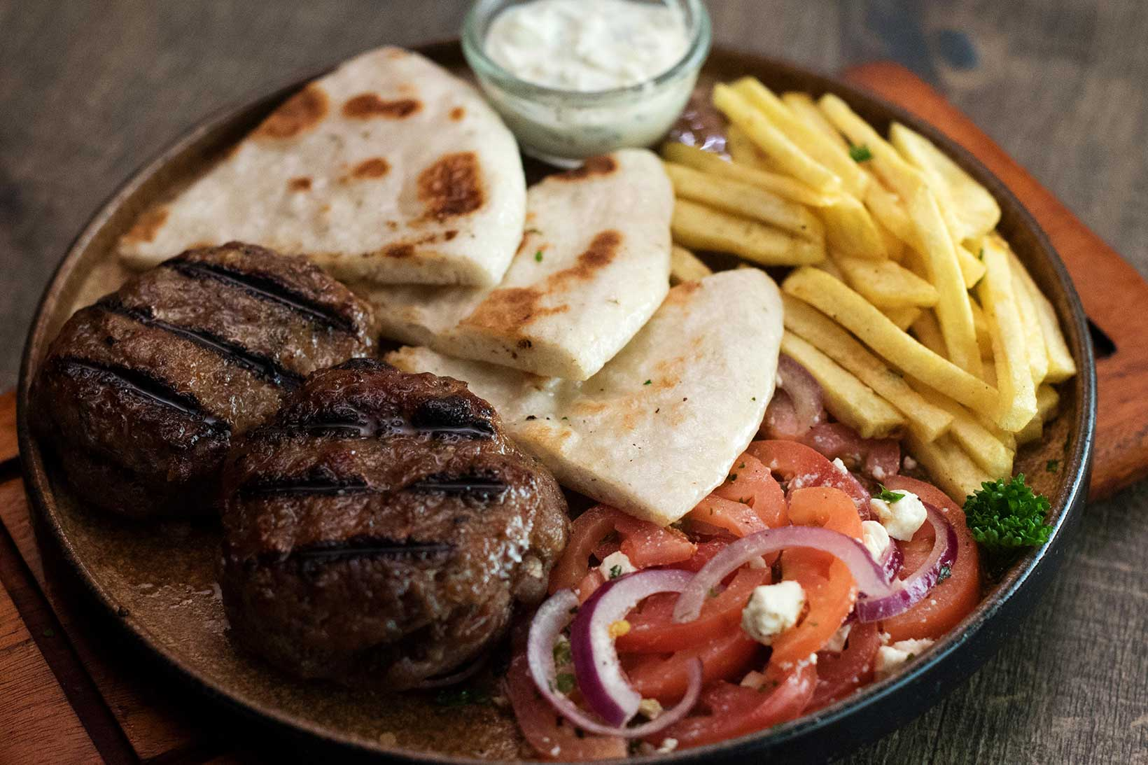 Beef and pork patties, stuffed with feta and tomato cheese, served with pita or rice and salad tasty finish.