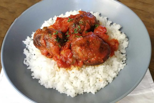 Deeply enriched and spiced meatballs coated in a traditional tomato sauce and served on a bed of rice