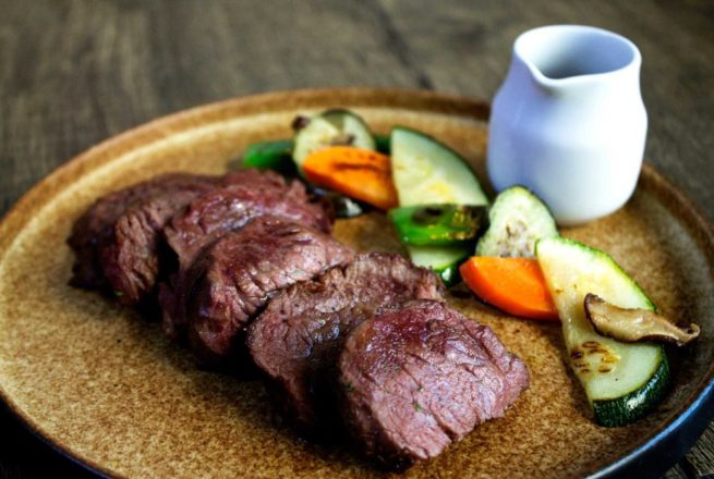 Grilled Angus Tenderloin Steak served with roasted vegetables and potatoes.