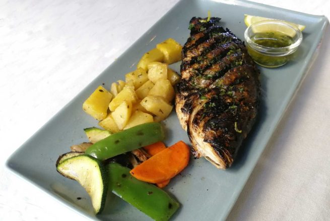 Olive oil infused grilled sea bass served with roasted herb potatoes and lemon wedge.