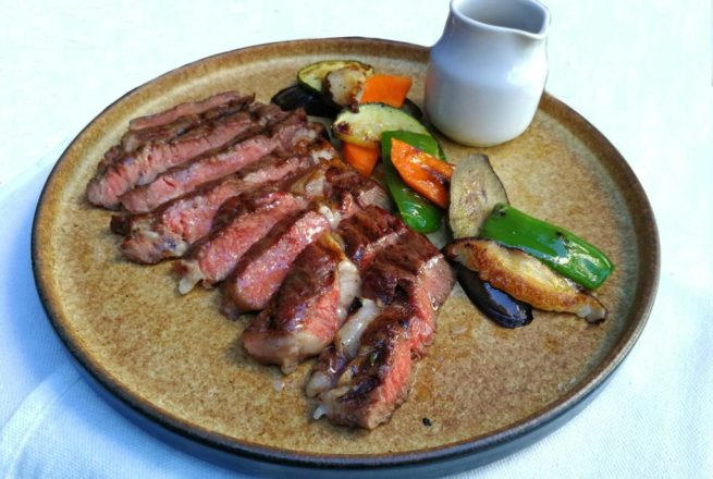 Grilled Rib Eye Steak served with roasted vegetables and potatoes.