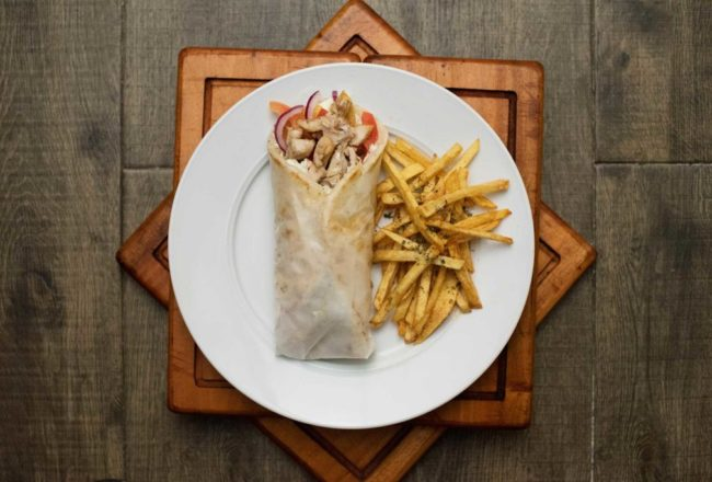 Sliced seasoned pork or chicken gyros wrapped on a warm pitta bread filled with fresh tomatoes, onions, fries and tzatziki.